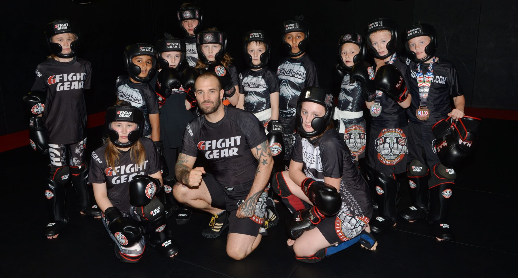 Pictured at the GLADIATOR MMA GYM, THE NEST UNIT 18, TRENT TRADING PARK, MELVILLE STREET, HANLEY, ST1 3LY as local MMA fighters win medals at a recent event in Fenton, having entered at just 10 days' notice.  Pictured left to right are 10-year-old Amy Clarke who won silver in the 40kg+ seven-10-years section, Charlie Robinson, aged nine, who took bronze in the same event as brother Bailey Robinson, aged 10, who took silver in the -40kg weight division having met each other in the semi-finals and  Reece Grocott, aged 13, who took gold in the +55kg category of the 11-14 year-olds section.   Team pic with all the fighters with Ross Pointon centre.